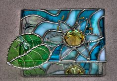 Stained glass lily pad and dragonfly jewellery/jewelry box commission. Beaded dragonfly, aqua blue waterglass, iridescent blue opal glass, antique clear glass, mirrored base, large yellow glass jewel. Decorative soldering water droplets on flower and lily pad.