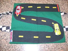 Love this idea! A homemade toy car carrier..has pockets on the outside for matchbox cars, and you open it up for the race track!