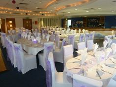 Venue Dressing- Lavender organza Sashes on white chair covers.