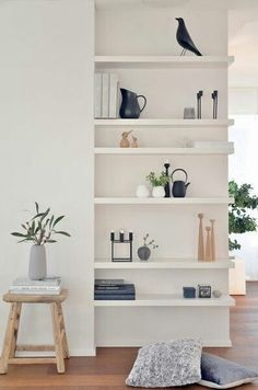 Minimalist white shelving against a white wall, with greenery