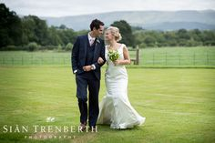 Bride and groom at Llangoed Hall with mountains in the background.