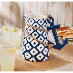Hand-painted ceramic pitcher features clever anchor handle sculpt and real jute rope detail.