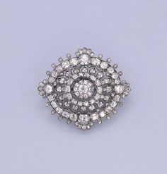 AN ANTIQUE DIAMOND BROOCH   The concave openwork oval-shaped panel with three tiers of old-cut diamonds to the central cluster, mounted in silver and gold, later rhodium plated, circa 1890, 5.8 cm. wide