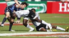 Scotland's Colin Gregor fights to keep hold of the ball against Fiji's Vilitati Nadialobo during their Sevens World Series Cup match in Dubai.