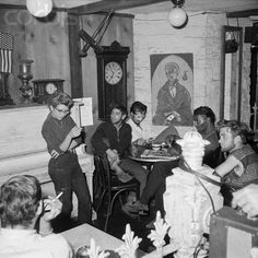 New York, New York: Inside the Beatnik street level coffee shop, the Beatniks make their own entertainment. At the moment, all eyes are on the girl standing by the piano and reciting poetry.  Date Photographed: August 1, 1959