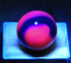 Rare vintage blue swirl on yellow base Akro Agate marble -- glows mulberry pink under black light/UV light.
