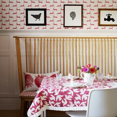 Single-colour motifs in a pink hue adorn this dramatic dining room, from the tightly-packed motif design on the tablecloth, to the freer, quirky pattern on the wallpaper   Homes & Gardens