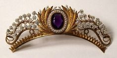 This is a French Empire tiara top. It would have a brass comb underneath attaching it to a chignon. It has pearls and a large amethyst at the center. c. 1840.
