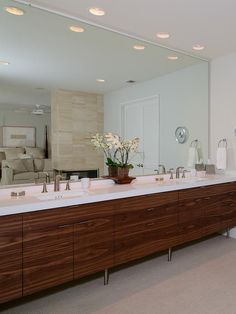 This vanity spans wall to wall, providing plenty of space for getting ready for the day ahead. A sleek white countertop provides a nice contrast to the rich wood cabinets, while the bedroom is reflected in the large vanity mirror.