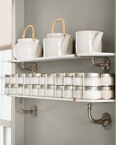 """Sneak in more shelves! """"In a kitchen, unused wall space is wasted space,"""" Martha says. Thin shelves -- these are antique milk glass -- add storage without feeling heavy or imposing, even in a tight spot. These hold teapots and spices (metal tins keep light out so spices last longer)."""