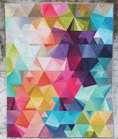 This special edition pattern features the Ombre collection by V and Co. for Moda Fabrics. Each quilt kit includes: - (19) half yard cuts from the Ombre collection (all colors except Black) - 3/4 yards