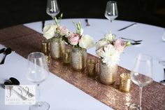A little sparkly table decor, with a rose gold sequin table runner, gold glitter jars with flowers and gold mercury glass tealight holders.