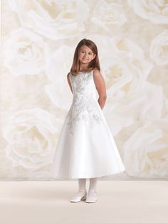 Sleeveless satin tea-length A-line dress accented with re-embroidered metallic lace appliqués on front and in back, covered buttons down back bodice, ideal as a First Communion dress or flower girl dress. Also available in half sizes 8½ – 14½ in White only. Sizes: 4 – 14, 8 ½ – 14 ½