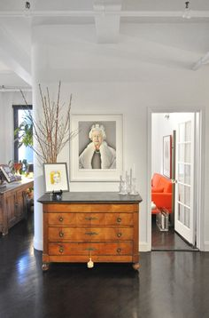 Loft entryway with antique dresser and image of the Queen of England