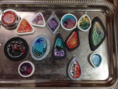 polymer clay bezels filled with fantasy paints waiting for resin top coat
