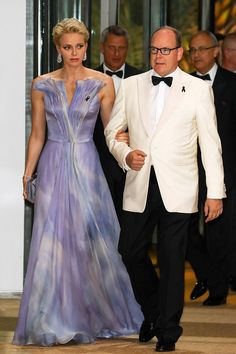 Princess Charlene wears a stunning floor-length purple evening gown. She added serious sparkle to her ensemble with a pair of weighty drop diamond earrings and a matching bracelet. Prince Albert wore his favorite white dinner jacket worn with a smart black bow tie and a lapel ribbon.