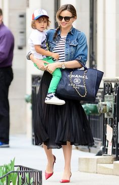 Miranda Kerr in a denim jacket + striped tee + black pleated skirt + red kitten heels