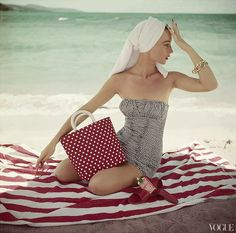 Model seated on striped beach towel wearing grey and white patterned strapless bathing suit. Condè Nast Archive 1954. Photo: Roger Prigent.