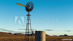 Stock Footage of A static (medium shot) timelaspe of a windmill and old farm dam with clouds in the distance as the golden sun sets over a mountain landscape. Explore similar videos at Adobe Stock