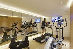 Neben dem Kino-Raum sehen wir das voll ausgestattete Hause Fitnessstudio mit natürlichen Holzvertäfelung und volle Höhe, rahmenlosen Spiegel den Raum Belichtungsreihe.