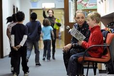 IS2 Jenna Welsh, from USS Blue Ridge (LCC 19), reads with a child during a community service project at Sullivans Elementary School. Jenna, her shipmates and Sailors from U.S. 7th Fleet staff visited a pet shelter, residential tower and local schools as part of a base-wide community service event.