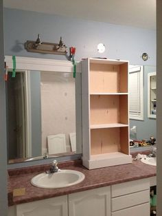 large bathroom mirror redo to double framed mirrors and cabinet, bathroom ideas, home decor, shelving ideas, middle cabinet in place new light fixtures connected and now onto the framing of the mirrors Bathroom Mirror Redo, Diy Mirror, Bathroom Fixtures, Bathroom Ideas, Mirror Ideas, Bathroom Lighting, Bathroom Shelves, Bathroom Cabinets, Vanity Redo