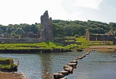 Stepping stones lead across the River Ogmore to the ruins of Ogmore Castle in Vale of Glamorgan, South Wales