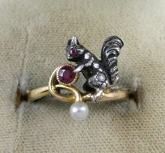 This antique squirrel ring is just super cute. Looks like gold with a pearl and amethyst, maybe the squirrel is sterling silver.