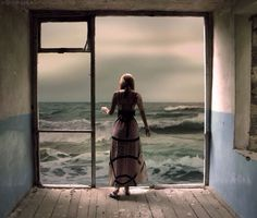 Woman standing at open window & water view art