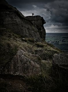 A young couple stare out upon the magnificent view from the Cow and Calf in Ilkley. The rolling Yorkshire valleys bare forth into the darkening horizon. Storm clouds form above the stone like blackened ashes. Hand in hand against the world, sweet adventure awaits.