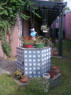 """Gorgeous 100-years-old """"aljibe"""" (water well) decorated with vintage iron pitcher and many plants and cacti. From my aunt & uncle's house in Venado Tuerto, Santa Fe, Argentina :)"""