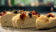 Zutaten: 500 g Mehl (Typ 812) 1 gehäufter Esslöffel Grieß 2 Beutel Trockenhefe 50 ml Olivenöl, plus ein wenig mehr 75 g schwarze Oliven, entsteint und in Scheiben geschnitten 150 g sonnengereifte Tomaten 2 – 3 Rosmarinzweige, nur die Blätter Meersalz und frisch gemahlener, schwarzer Pfeffer  Focaccia mediterran: Das Rezept von Gordon Ramsay