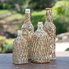 Rattan Covered Clear Glass Bottles: Great for homes with coastal- or natural-inspired design, this set of four clear glass bottles are covered with woven rattan and varied patterns to add intrigue and natural style.