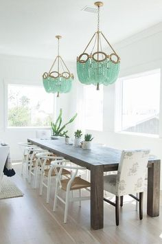 Chic dining room features a gray dining table, Crate & Barrel Big Sur Charcoal Dining Table, lined with white wishbone dining chairs and white and gray upholstered captain dining chairs illuminated by mint green beaded chandeliers, Ro Sham Beaux Fiona Chandeliers, placed in front of picture windows.