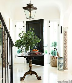 """To create a light, airy feel in the entry of his West Hollywood house, visual merchandiser Mark D. Sikes painted the walls New Linen by Kelly-Moore and whitewashed the floors. For a dramatic """"Dorothy Draper moment,"""" he used Benjamin Moore's high-gloss Black on the door.   - HouseBeautiful.com"""
