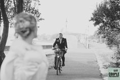 The groom cycles towards his bride on Clontarf Seafront . Weddings at Tulfarris Hotel Photographed by Couple Photography.