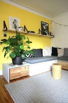 salon mur jaune canari, banquette faite sur mesur et étagères en ceintures / Living room with yellow wall, shelves made with belt and a handmade bench