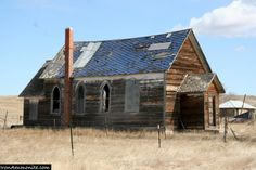 The abandoned Catholic church, with its arched windows, looks lonely against the wide-open South Dakota sky.