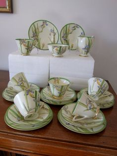 Doulton deco: Iris tea set including tea trios, V1346, c1933 (pattern). Blue irises and green foliage, including floral motif to inner cup rim, with green bands and gold gilt highlights and trim.