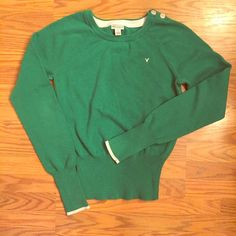 """American Eagle crew neck kelly green sweater American Eagle green sweater. Beautiful kelly green color! Cream colored at hands. Very soft! Button detail adorning one shoulder. Ribbed/banded at wrists and waist. Measures 23"""" in length, 15"""" across chest, & 25"""" from pit to hand. Worn twice and in EUC. Size medium. ❤️NO TRADES. Reasonable offers accepted via offer button.❤️ American Eagle Outfitters Sweaters Crew & Scoop Necks"""