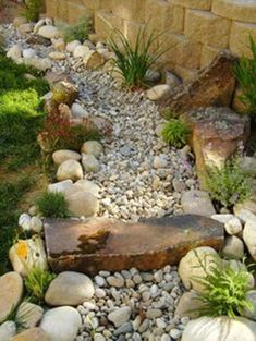 The line where your lawn meets the fence can be used as the perfect spot for a dry creek bed. Plan it out, dig the area, and then begin filling it with stones, rocks, and plants. You could even create a cute little rock bridge like the one shown here. It's a great way to use an area otherwise untouched and add some visual interest to your backyard. #landscapefrontyardwithstone