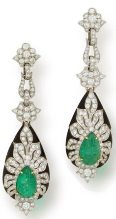 A pair of carved emerald, diamond and onyx pendant earrings  each designed as cascade of stylized floral and foliate round brilliant-cut diamond elements, suspending a carved pear-shaped emerald cabochon surrounded by round brilliant-cut diamonds and calibré-cut onyx; estimated total diamond weight: 3.65 carats; mounted in platinum; length: 2 3/4in. Via Bonhams.