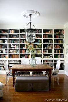 emilyaclark.com dining room with bookshelves, gray bench, farmhouse table