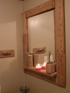 framed my bathroom mirror with pallets, the towel hanger is a piece of pallet and an old drawer handle. I made the candle holders out of pieces of wood and the plant holder is a jar wrapped with jute.