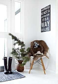 Bright entryway with a decorative spruce branch and a wooden christmas wreath.