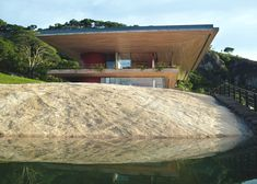 This home and recording studio for a musician by Sforza Seilern Architects perches between overhanging slabs on a huge boulder overlooking a dam in Africa.