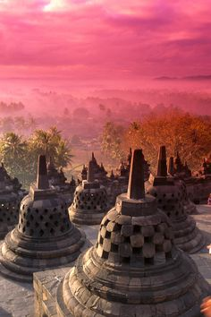 "View of City at Pink Sunrise, Java, Indonesia - - the old temple of Borobudur, and each of these ""bells"" is a stupa-cage that protects stone buddhas that sit inside. Beautiful!"