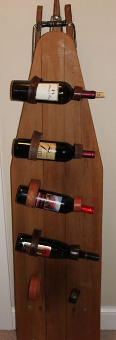 Old ironing board and belt straps make an interesting wine rack.