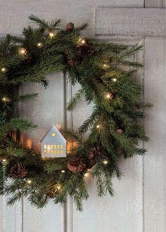Couronne de noël en sapin avec une guirlande lumineuse et une petite maison illuminée à accrocher à sa porte pour décorer son extérieur pendant noël