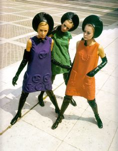 PIERRE CARDIN Haute Couture 1968. Tamara Tanya & Tina wearing purple green & orange tunics with black rubber thigh high boots, gloves & hats. Great for that mod s&m party. From Pierre Cardin 50 Years of Fashion & Design. (minkshmink)